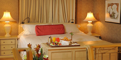 Suite King bed with breakfast on a tray