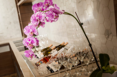 Pink moth orchid next to champagne bottles and flutes